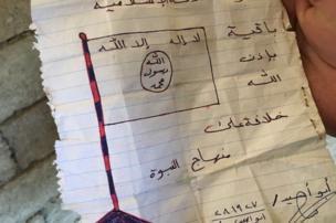 ورقة عثر عليها في أحد المنازل تصور العلم الذي يستخدمه مسلحو تنظيم الدولة الإسلامية