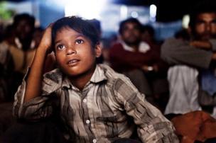 ટ્રાવેલિંગ સિનેમા નિહાળતા બાળકનો ફોટો