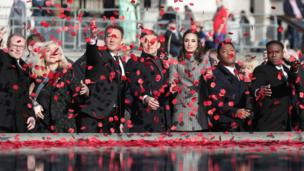 People throw poppies into the Trafalgar Square fountain to mark Armistice Day
