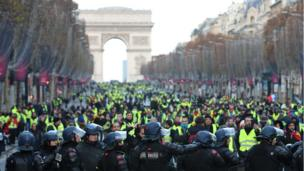 Protesters wearing yellow vests walk on the Champs-Elysees Avenue with the Arc de Triomphe in the background
