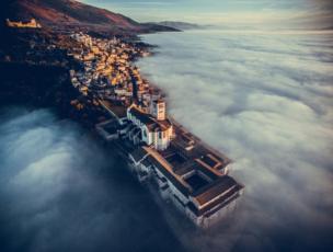 มหาวิหารเซนต์ฟรานซิสแห่งเมืองอัสซิซี ในแคว้นอุมเบรีย ของอิตาลี งดงามและโดดเด่นท่ามกลางทะเลหมอกหนาทึบและแสงอาทิตย์ที่ฉาบอยู่ที่หอระฆัง