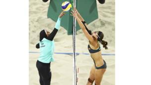 Doaa Elghobashy de Egipto cubierta de los tobillos a la cabeza, y la alemana Kira Walkenhorst en un bikini en un partido de voleibol playa