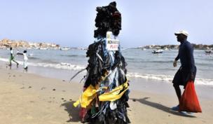 """ويوم السبت، وعلى الجانب الآخر من القارة، شوهد """"وحش بلاستيكي"""" يسير على طول الشاطئ في داكار بالسنغال، في احتجاج على النفايات البلاستيكية."""