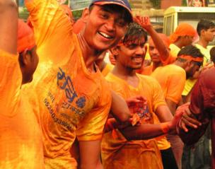 A group of men painted orange and dancing in the rain