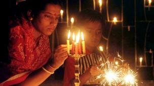 દિવાળીના તહેવાર પર દીપ પ્રજ્વલિત કરતી મહિલા અને ફૂલઝર સાથે બાળકની તસવીર