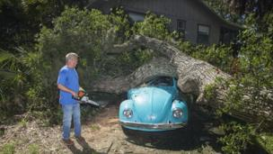 Tom Reams looks over a tree on top of his 15 year old daughter's Volkswagen Beetle and house cause by the wind and storm surge from Hurricane Hermine at Alligator Point, Florida 2 September 2016.