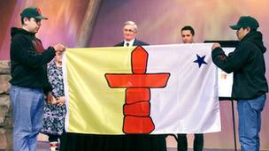 Canadian Governor General Romeo LeBlanc looks on as flag unveiled at official ceremony to inaugurate Nunavut, 1999.