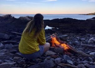 A girl toasts marshmallows on the campfire
