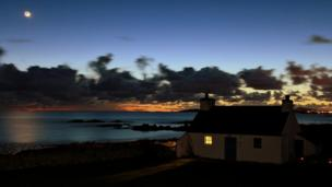 Sunset over a little cottage at Porth Nobla, Anglesey