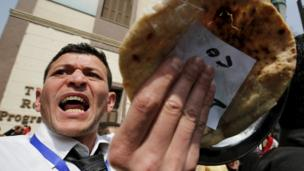A man gestures with a piece of bread during a protest, to demand the government to offer unemployed graduates jobs, in front of the parliament headquarters in Cairo, 27 March 2016, where Egyptian Prime Minister Sherif Ismail was speaking.