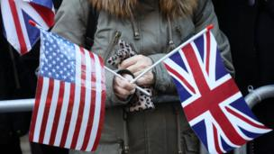 Nhiều người trong đám đông vẫy cờ Anh và cờ Mỹ trước cửa hội chợ từ thiện của Terrance Higgins Trust để chào mừng Hoàng tử Harry và vị hôn thê người Mỹ.