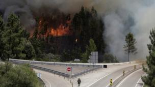 Humo y fuego en la carretera IC8 por el incendio forestal cerca de Pedrogao Grande, en el centro de Portugal, el 18 de junio de 2017.