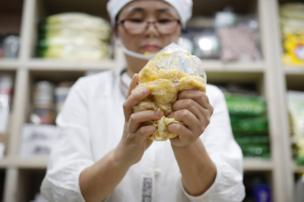 North Korean defector Hong Eun-hye demonstrates how North Korean people make rice cakes with corn powder at her North Korean food store in Seoul, South Korea, 28 September 2017.