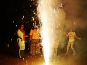 A group of people excitedly gather round a large sparkler as it burns and fills the night with light