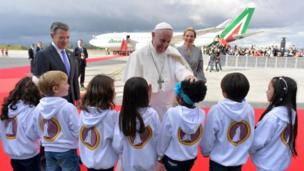 Colombian President Juan Manuel Santos (L) and his wife Maria Clemencia Rodríguez (R) look on as Pope Francis (C) greets children after disembarking from an aircraft upon his arrival at Bogotá on 6 September 2017.