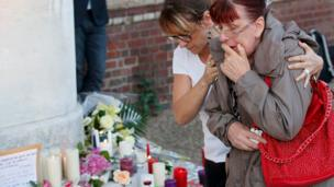 Women reacts at memorial for priest