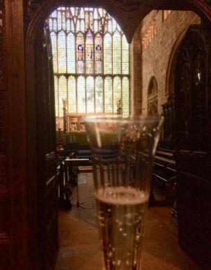 A glass of Prosecco is held up towards the large stained glass church windows