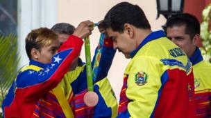 Venezuelan boxer Yoel Finol, who won bronze in the Men's fly 52kg event at the Rio 2016 Olympic Games, places the medal around the neck of Venezuelan President Nicolas Maduro (right) during a welcome ceremony in Caracas