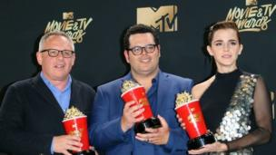 "Director Bill Condon (L) stands with actors Josh Gad (C) and Emma Watson (R), winners of Movie of the Year for ""Beauty and the Beast"" in the press room during the 2017 MTV Movie ^ TV Awards at the Shrine Auditorium in Los Angeles, California, May 7, 2017."