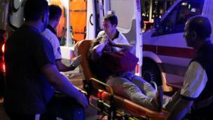 Una mujer herida se cubre el rostro mientras es trasladada por paramédicos tras el atentado en el aeropuerto de Estambul.