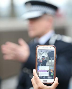 Mark Rowley, Assistant Commissioner for Specialist Operations in the Metropolitan Police, is filmed on a smartphone outside Scotland Yard in London