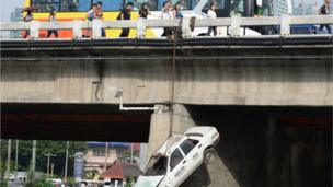 Pedestrians walk past a car suspended along a bridge in an earthquake drill as part of the metro-wide quake drill in Manila on June 22, 2016.