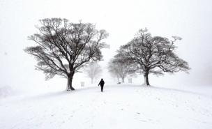 People walk through the snow at Lyme Park, Cheshire.