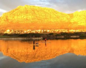 Two people take their dogs out for a paddle in a marina as the golden sun lights the mountain in the background