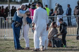 افسر پلیس نیوزیلند، خانواده یکی از داغداران کرایست چرچ را در آغوش گرفته و دلداری میدهد