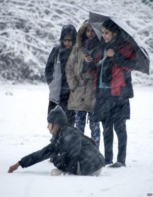 जम्मू कश्मीर की राजधानी श्रीनगर में इन दिनों बर्फ़बारी हो रही है, ऐसी ही बर्फ़बारी के बीच छाता लिए सेल्फ़ी खींचती कुछ युवतियां.