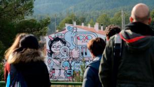 People look at a street art mural on the facade of a house in Fanzara near Castellon de la Plana