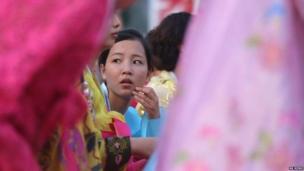 आर्थिक अडचणी असतानाही दरवर्षी राजधानील विशाल परेडचं आयोजन केलं जातं. फोटोमध्ये दिसत असलेली मुलगी परेड सुरू होण्याची वाट पाहत आहे.