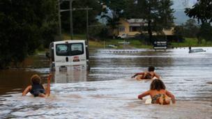 أشخاص يتزلجون في شوارع مدينة بيلنيودجل الأسترالية بعد أن غمرتها مياه الفيضانات.