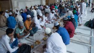 مسلمون يتناولون إفطارهم في المسجد الجامع في دلهي بالهند