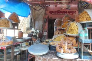 A man prepares food in a street stall fall of snacks