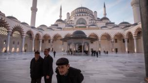 صورة من ساحة المسجد وبها ثلاثة رجال مسنين