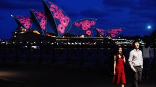 A couple poses by sails of the Sydney Opera House are seen illuminated with red poppies to commemorate Remembrance Day, also known as Armistice Day, in Sydney, Australia, 11 November 2017