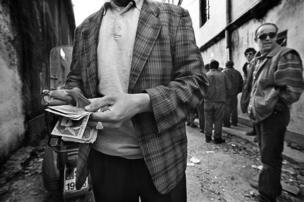 رجل يعد نقودا في ألبانيا.