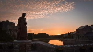 The Henry VII statue looking out to a sunset beside Pembroke Castle.