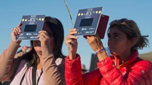 Dos mujeres ven el eclipse mediante protectores
