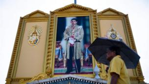 A man walks past a portrait of Thailand's King Maha Vajiralongkorn near the Grand Palace in Bangkok on May 3