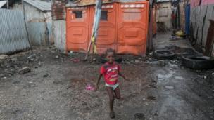 Mtoto akicheza nje ya nyumba yao kwenye mtaa wa mabanda mjini Port-au-Prince, Haiti