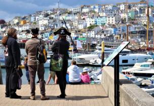 Dressed in pirate costumes, three people look over the pier at the boats