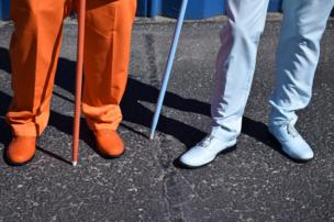 One man wears orange trousers, shoes and holds an orange cane, with the man next to him wearing all pale blue