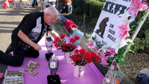 روجر إنلباي من ولاية ميسوري الأمريكية يؤسس نصبا لإلفيس خارج بوابات غريسلاند أثناء انتظاره بدء تجمع لإضاءة الشموع أحياء لذكرى إلفيس بريسلي الأربعين.