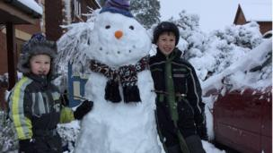 Two boys with a snowman