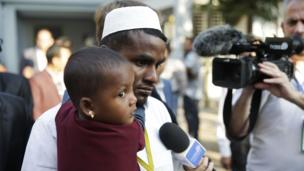 A Rohingya man and child wait to meet the Pope in Dhaka
