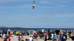 Spectators on the East Strand watch the Catalina plane at the Air Waves Portrush Northern Ireland International Airshow