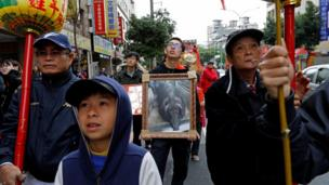 """A family member of the owner of winner of the """"holy pig"""" contest holds a photo of the animal during a parade in Sanxia district, in New Taipei City, Taiwan, 2 February 2017."""