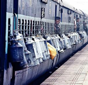 Milk cans are tied to the outside of a train as milkmen peep out of the doors.